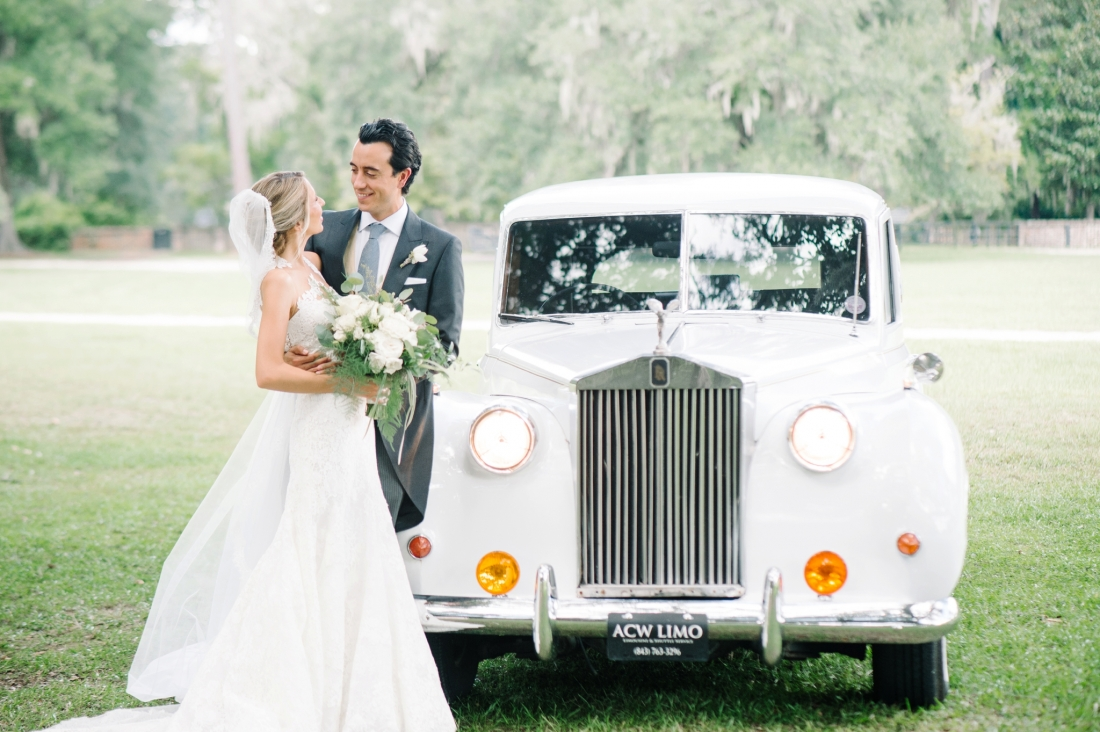 Nahila and Bernard in front of their vintage white Bentley at their Middleton Place wedding by Charleston wedding photographers Aaron and Jillian Photography_00108